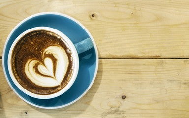 Hot coffee drawing heart in blue cup