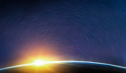 Landscape image of Earth, sunrise and star trail view from space. (Elements of this image furnished by NASA)