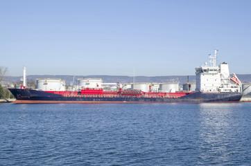 Big metal industrial oil tanks on port and  tanker