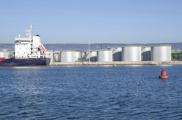 Big metal industrial oil tanks on port