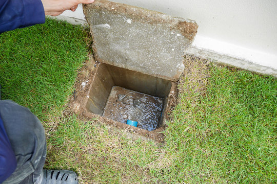 Worker hand open sewer of new house