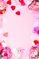 Beautiful pink rose, decorative confetti hearts and pink ribbon on pink Valentines day background