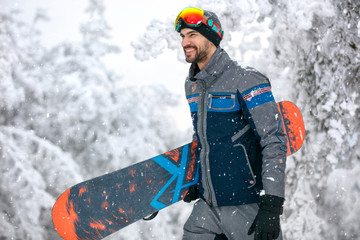 Snowboarder with snowboard going to ski terrain