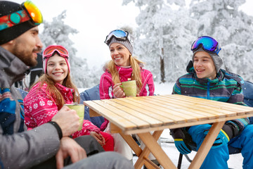 Family on ski terrain drinking tea