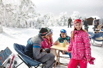 Girl with family in cafe on ski terrain enjoy