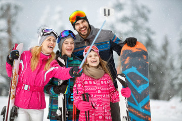 family taking selfie photo while skiing in snow