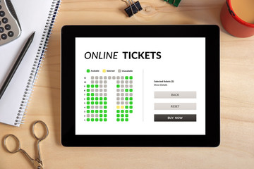 Online tickets concept on tablet screen with office objects on wooden desk. All screen content is designed by me. Top view