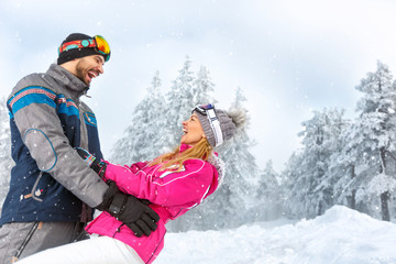 Man and woman having fun in snowy nature on mountain