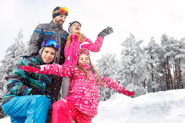 Children with parents in snowy nature at winter vacation