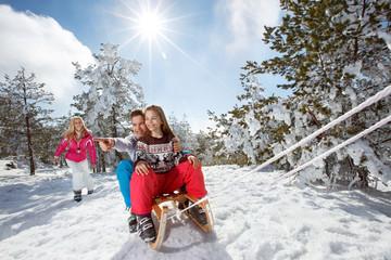 Children enjoying on sleds on winter holiday