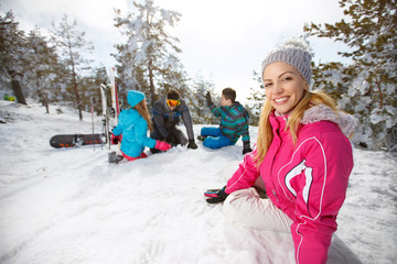 Woman with family enjoying on snow on skiing