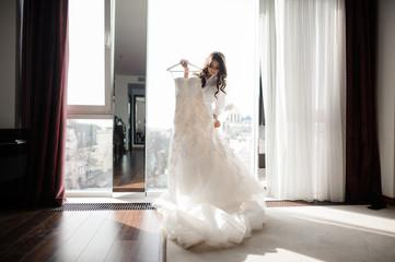 Bride holding wedding dress on a hanger near window