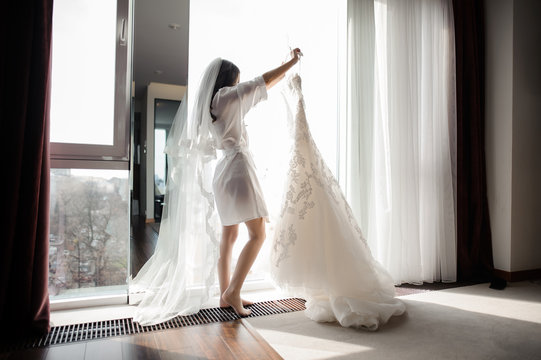 bride in dressing gown and veil holding wedding dress on a hanger