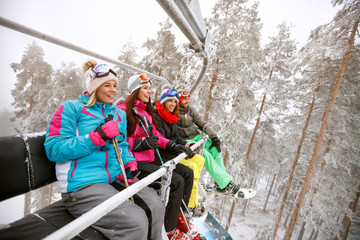 Women and man in ski lift together