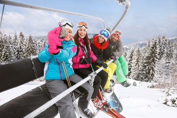 Female making selfie with friends in ski lift