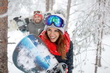 Woman with snowboard in forest