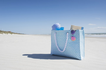 Bag with towel, book and sunglasses on empty beach
