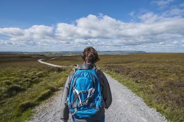 Ireland, Cavan County, Cuilcagh Mountain Park, Woman hiking along road