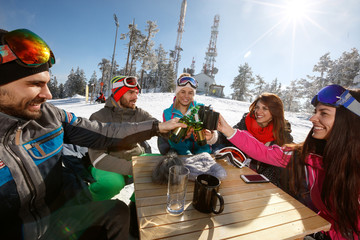 Skiers group toasts with drinks in cafe on ski terrain