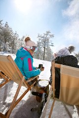 Two female in sun bed talking and resting from skiing, back view