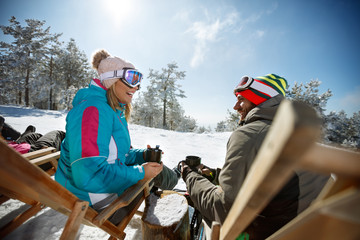 Couple in mountain enjoy in sunbed on ski terrain
