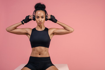 Fit woman with headphones sitting on box after workout