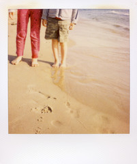 Photograph Of Siblings Legs Standing On The Beach