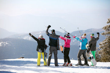 Skiers in mountain with ski sticks up, back view