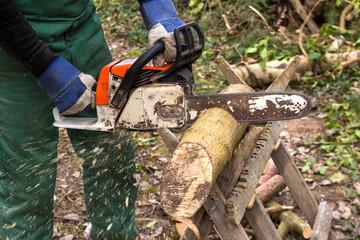 Mann mit Motorsäge sägt Holz für Kamin Brennholz Arbeit