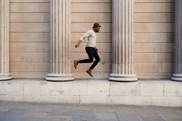 Man in hat and earphones jumping over stone building.