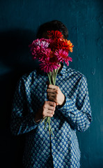 Young man hiding his face behind colorful flower bouquet