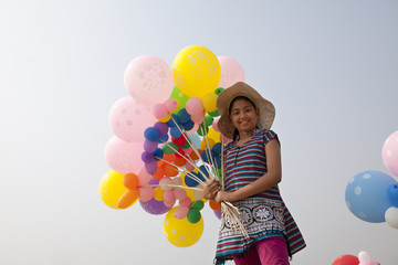 Teenage girl with colorful balloons in hand
