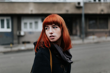 Young redhead woman walking in the streets