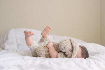 Baby lying down with bunny stuffed animal