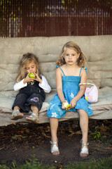 Sisters sit on a bench swing, eating apples