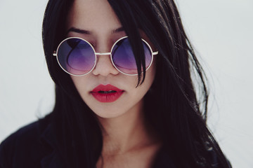 Closeup portrait of a sexy woman with red lipstick and sunglasses