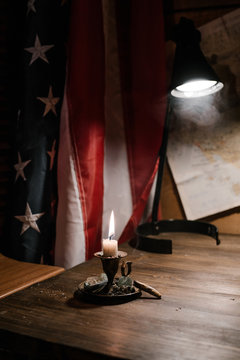 candle burns on a background of the American flag