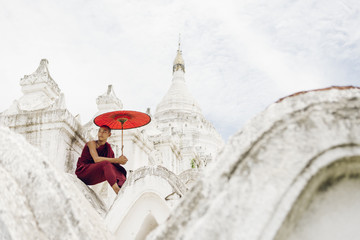 A novice Buddhist monk seated with a red umbrella in a Hsinbyume Temple