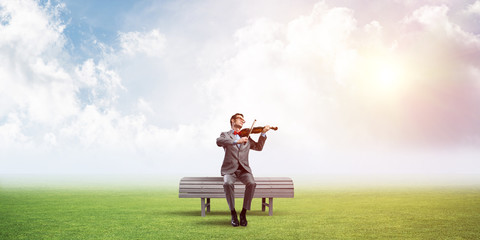 Handsome businessman in park on wooden bench play his melody