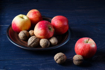 Apples and walnuts on a dark wooden background