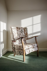 Armchair in the corner of a sunlit room
