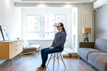 Young woman wearing virtual reality simulator while sitting in living room