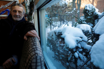 Tom Smith, who is homeless, sits for a portrait inside the Pine Street Inn, with snow covering the bushes outside, in Boston