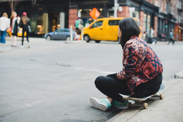 Skater sitting on curb in city