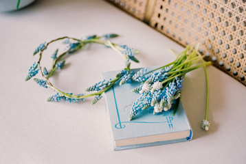 Floral wreath, bouquet and book on chair
