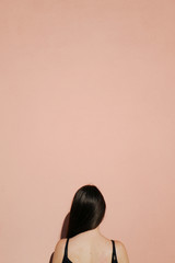 Back view of a woman against a pink wall