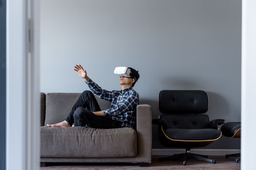 A young man wearing virtual reality headset at home