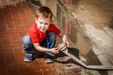 A cute puzzled boy looking at the fire hose wondering where the water is gone. Child at the fire station stock image.