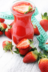 glass of strawberry smoothie and many fresh strawberries on a wooden background.