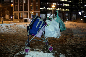 A homeless man's cart rests on the sidewalk as New York City's Coalition for the Homeless delivers food, donated clothing and supplies during winter storm Grayson in New York